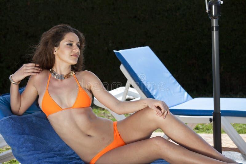 Kvinna i bikini på solstol arkivbild