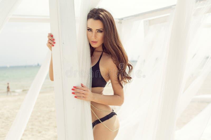 Kvinna i bikini på stranden med gardiner arkivfoto