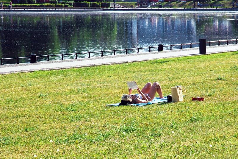 Kvinna i bikini som solbadar av dammet som ligger på gräs, läsningpappersbok royaltyfri foto