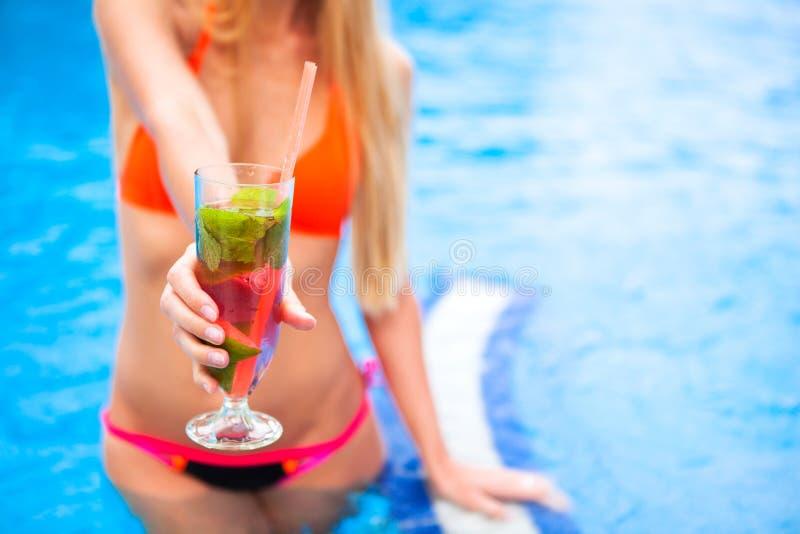 Kvinna i bikinihand med mojito för jordgubbe för coctailexponeringsglas nära royaltyfri bild
