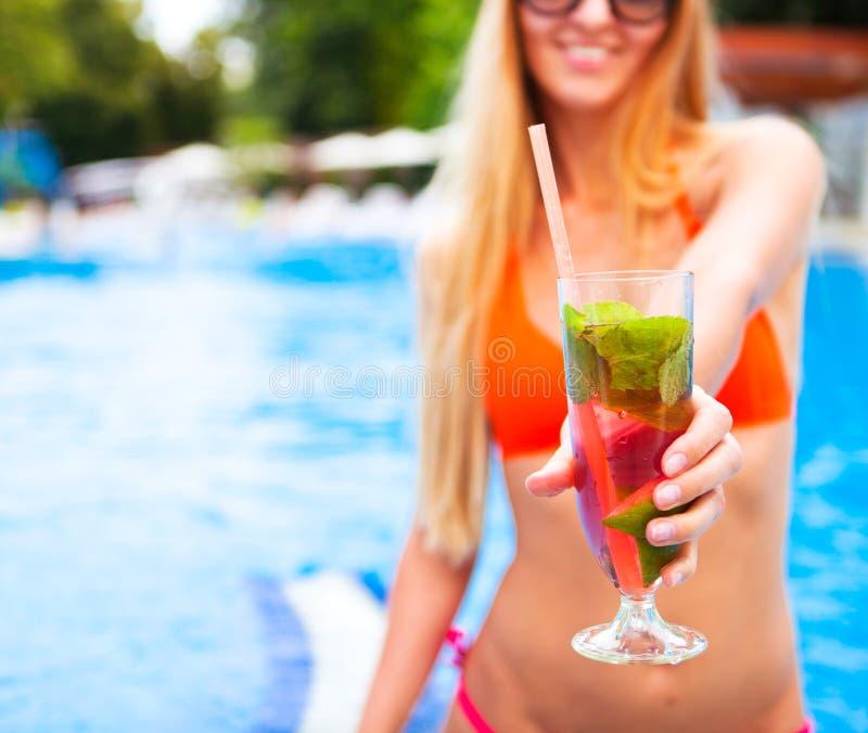 Kvinna i bikinihand med mojito för jordgubbe för coctailexponeringsglas nära royaltyfria bilder