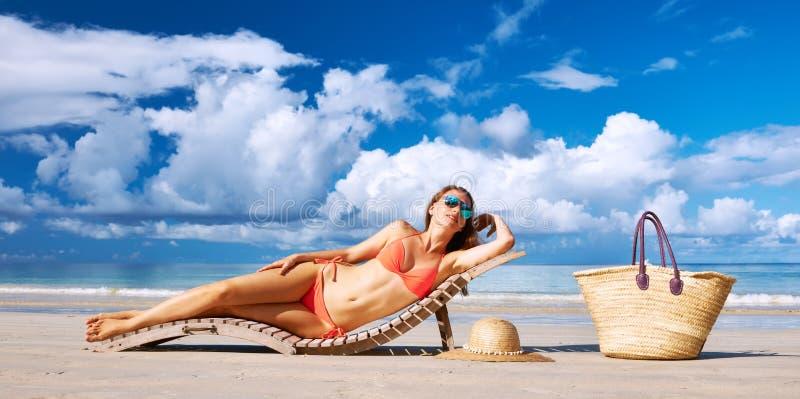 Kvinna i bikinin som ligger på stranden på Seychellerna royaltyfri foto