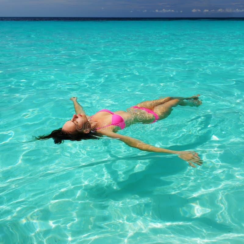 Kvinna i bikinin som ligger på vatten arkivfoto