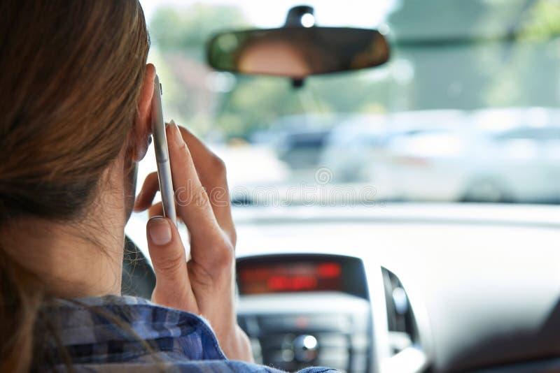 Kvinna i bil som talar på mobiltelefonstundkörning royaltyfri foto