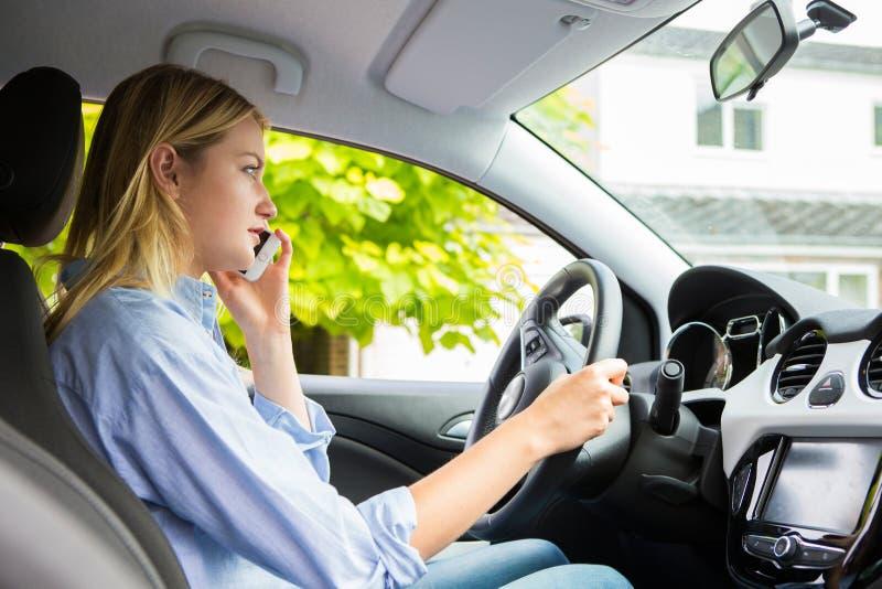 Kvinna i bil som talar på mobiltelefonstundkörning arkivbild