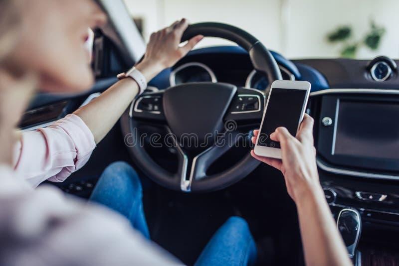 Kvinna i bilen genom att använda smartphonen arkivbild