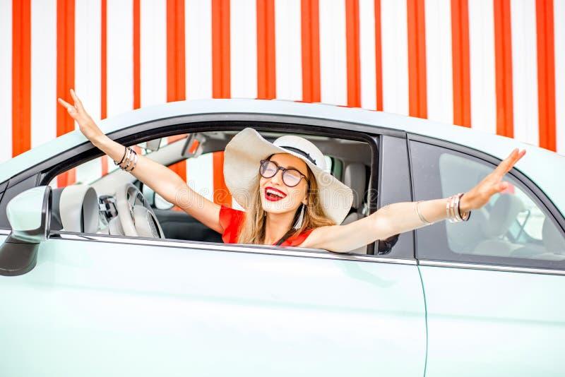 Kvinna i bilen på röd väggbakgrund royaltyfri fotografi