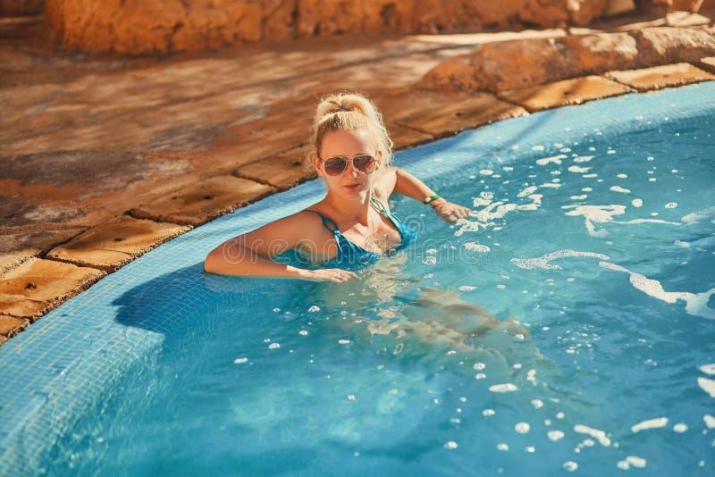 Kvinna i blå baddräkt och solglasögon som kopplar av i utomhus- pöl med rent genomskinligt turkosvatten royaltyfria bilder