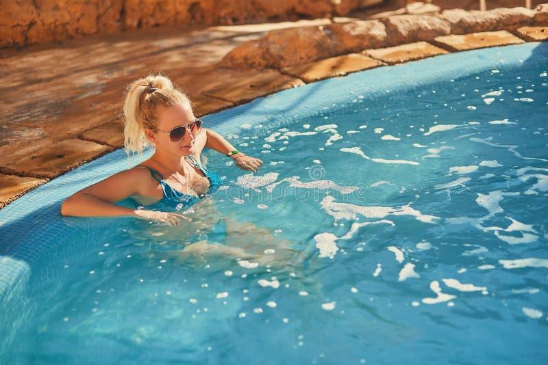 Kvinna i blå baddräkt och solglasögon som kopplar av i utomhus- pöl med rent genomskinligt turkosvatten royaltyfria foton