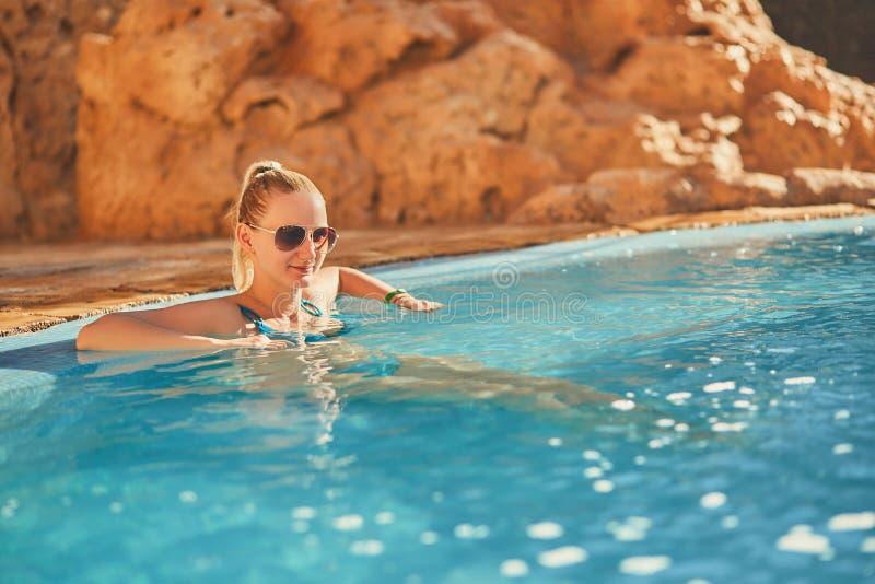 Kvinna i blå baddräkt och solglasögon som kopplar av i utomhus- pöl med rent genomskinligt turkosvatten royaltyfri foto