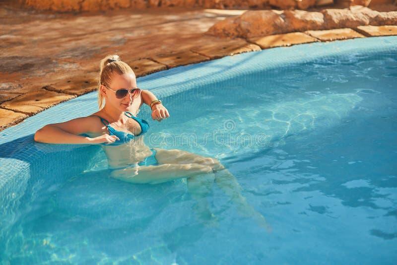 Kvinna i blå baddräkt och solglasögon som kopplar av i utomhus- pöl med rent genomskinligt turkosvatten royaltyfri fotografi
