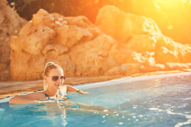 Kvinna i blå baddräkt och solglasögon som kopplar av i utomhus- pöl med rent genomskinligt turkosvatten Solsignalljus arkivbild