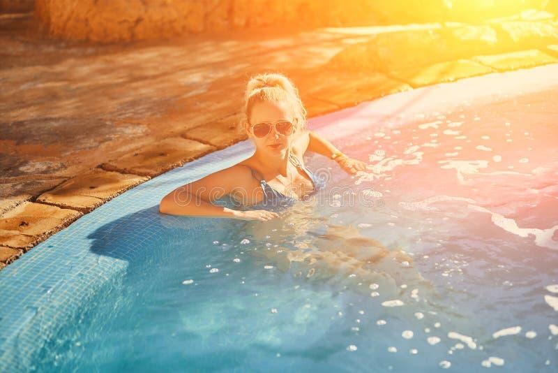 Kvinna i blå baddräkt och solglasögon som kopplar av i utomhus- pöl med rent genomskinligt turkosvatten Solsignalljus arkivbilder