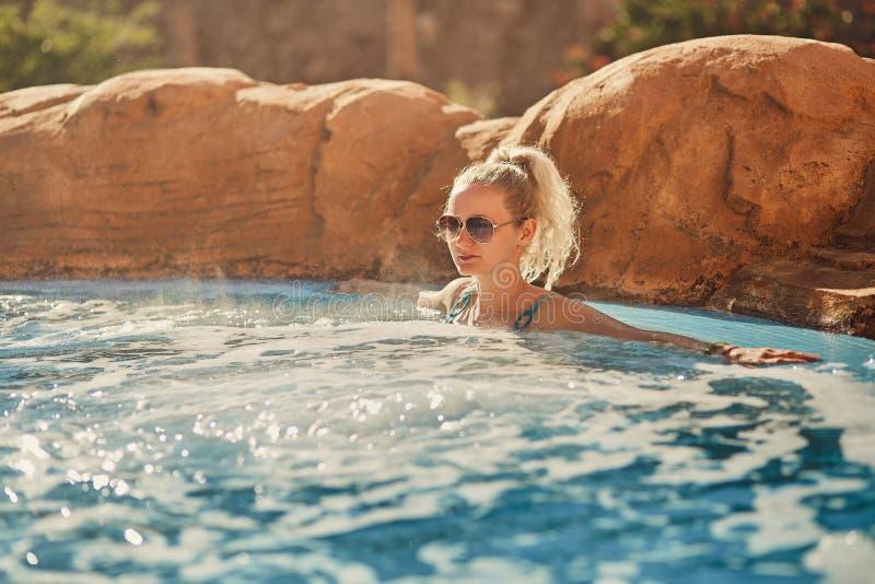 Kvinna i blå baddräkt som kopplar av i utomhus- bubbelpool med rent genomskinligt turkosvatten arkivbilder