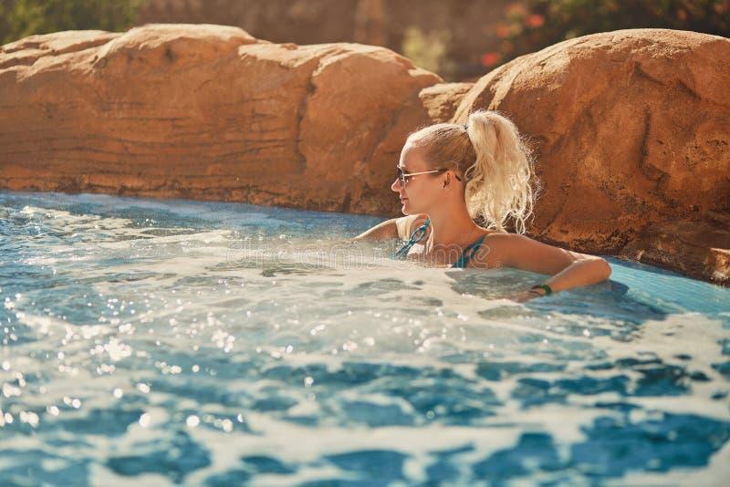 Kvinna i blå baddräkt som kopplar av i utomhus- bubbelpool med rent genomskinligt turkosvatten arkivfoton