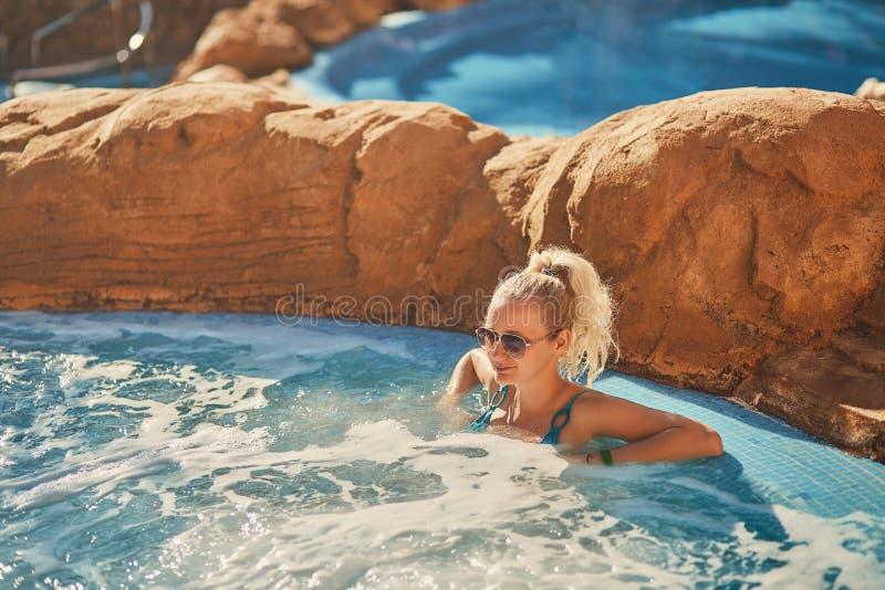 Kvinna i blå baddräkt som kopplar av i utomhus- bubbelpool med rent genomskinligt turkosvatten arkivbild