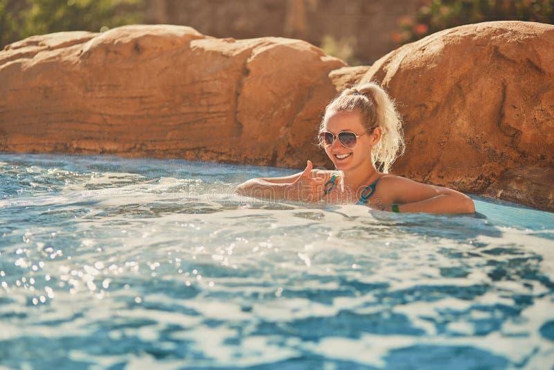 Kvinna i blå baddräkt som kopplar av i utomhus- bubbelpool med rent genomskinligt turkosvatten fotografering för bildbyråer