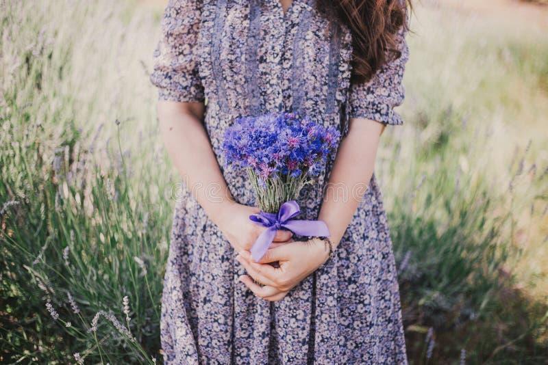 Kvinna i blå blom- klänning med blåklinter i händer arkivfoto