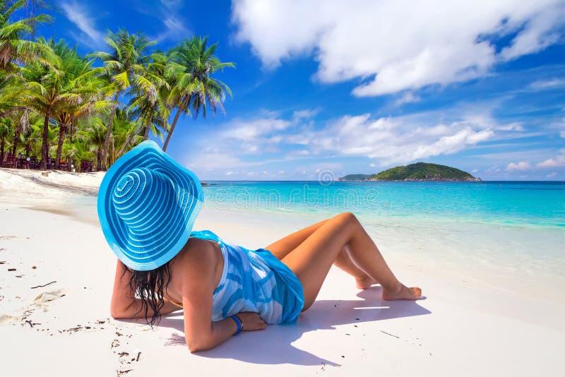 Kvinna i blå hatt på den tropiska stranden royaltyfri foto