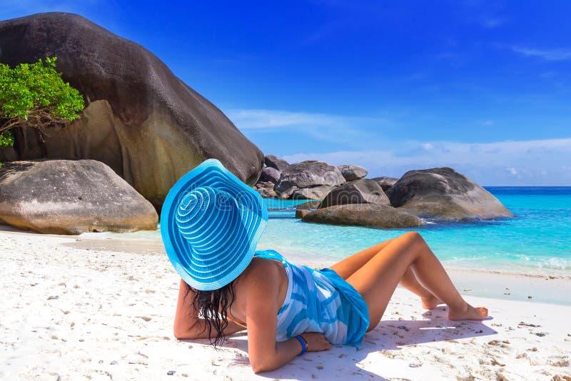 Kvinna i blå hatt på den tropiska stranden royaltyfria bilder