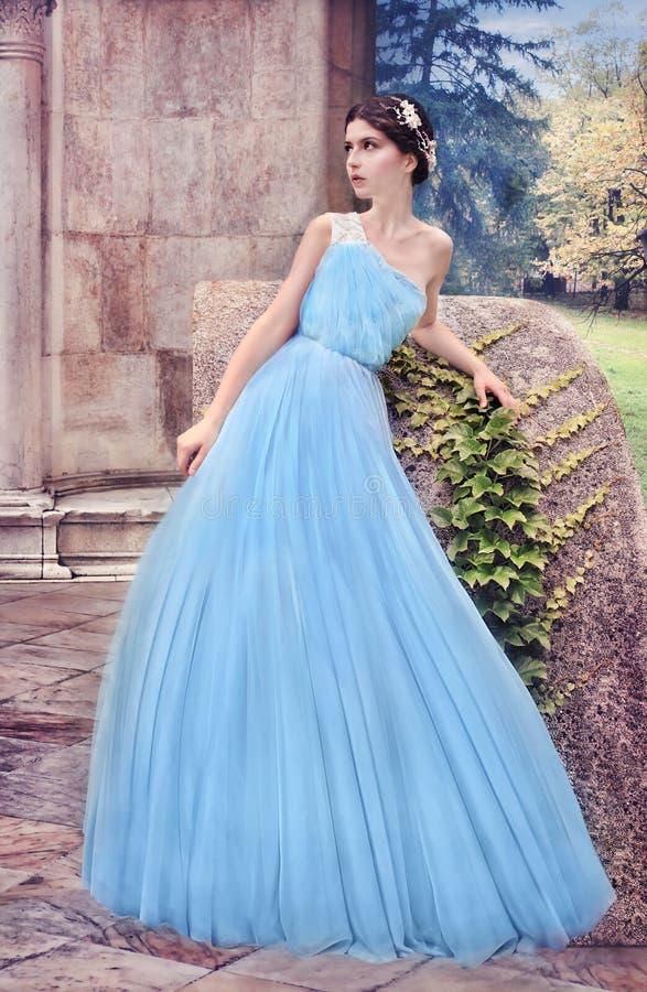 Kvinna i blå klänning, i den hemliga trädgården fotografering för bildbyråer