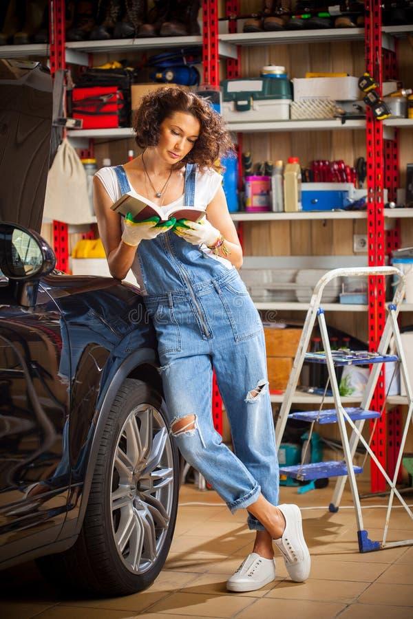 Kvinna i blåa overaller som studerar anvisningarna för medeljustering royaltyfri bild
