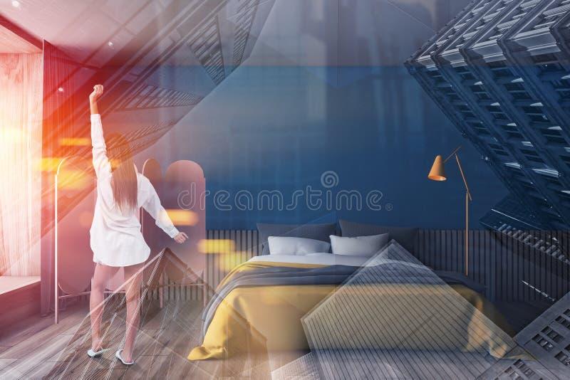 Kvinna i blått sovrum med gul säng arkivbild