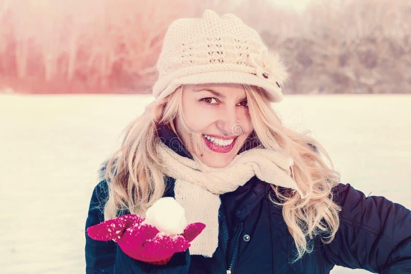 Kvinna i boll för snöinnehavsnö förestående för att kasta snöboll royaltyfri bild