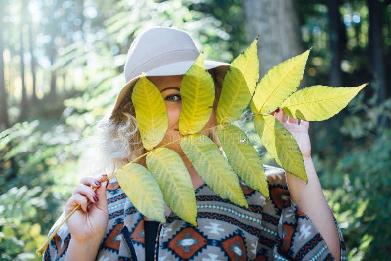 Kvinna i bredbrättad klädd med filt hatt och autentiska ponchon som döljer hennes framsida bak det stora trädbladet royaltyfri bild