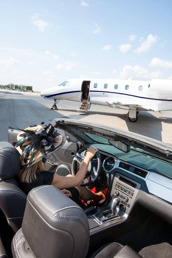Kvinna i cabriolet med privata Jet At Terminal arkivbilder