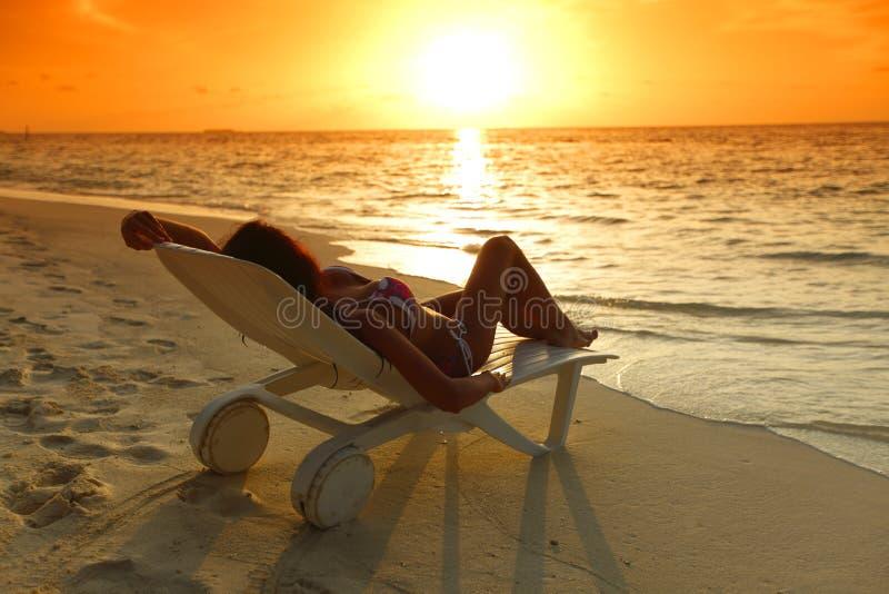 Kvinna i chaise-vardagsrum som kopplar av på strand arkivbilder