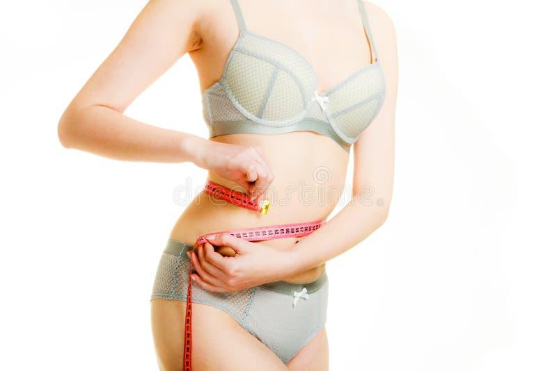 Kvinna i damunderkläder som mäter hennes midja med måttbandet arkivfoton