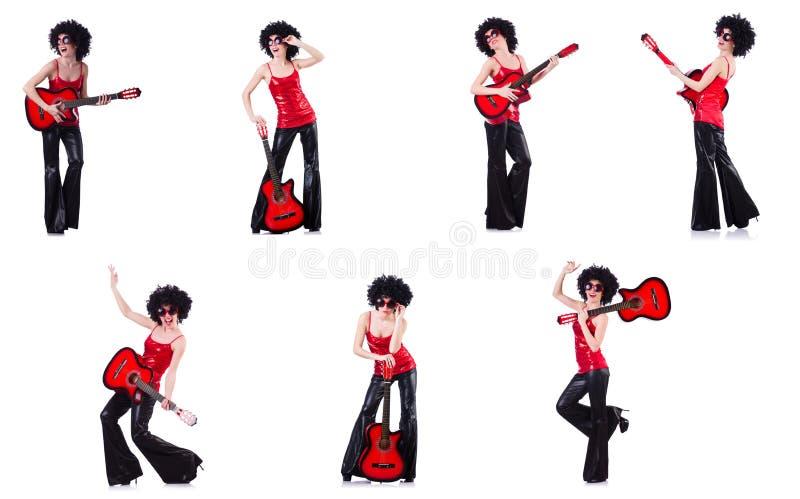 Kvinna i den afro peruken som spelar gitarren arkivfoto