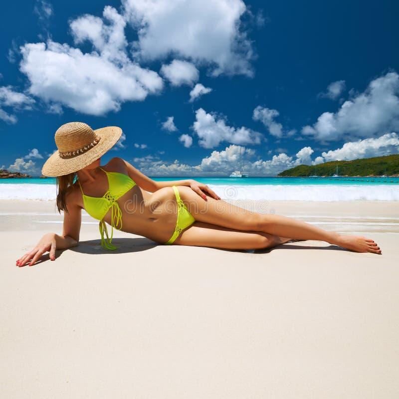Kvinna i den gula bikinin som ligger på stranden på Seychellerna royaltyfria bilder