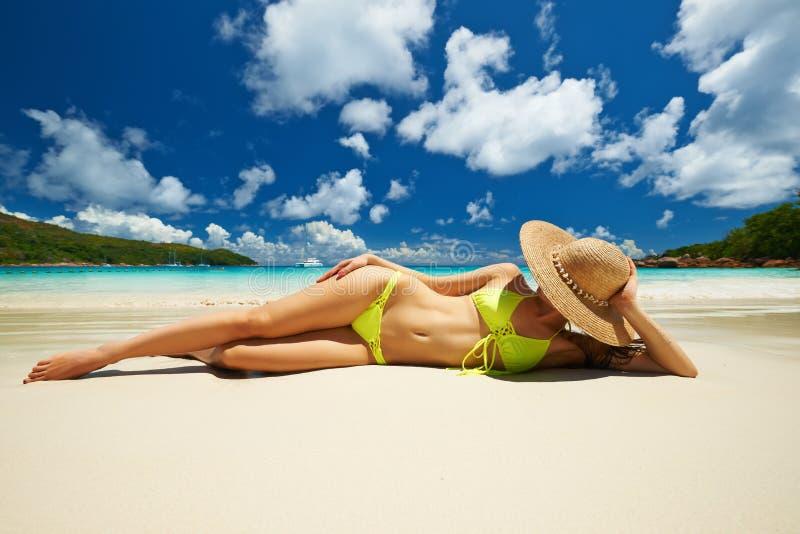 Kvinna i den gula bikinin som ligger på stranden på Seychellerna royaltyfri bild