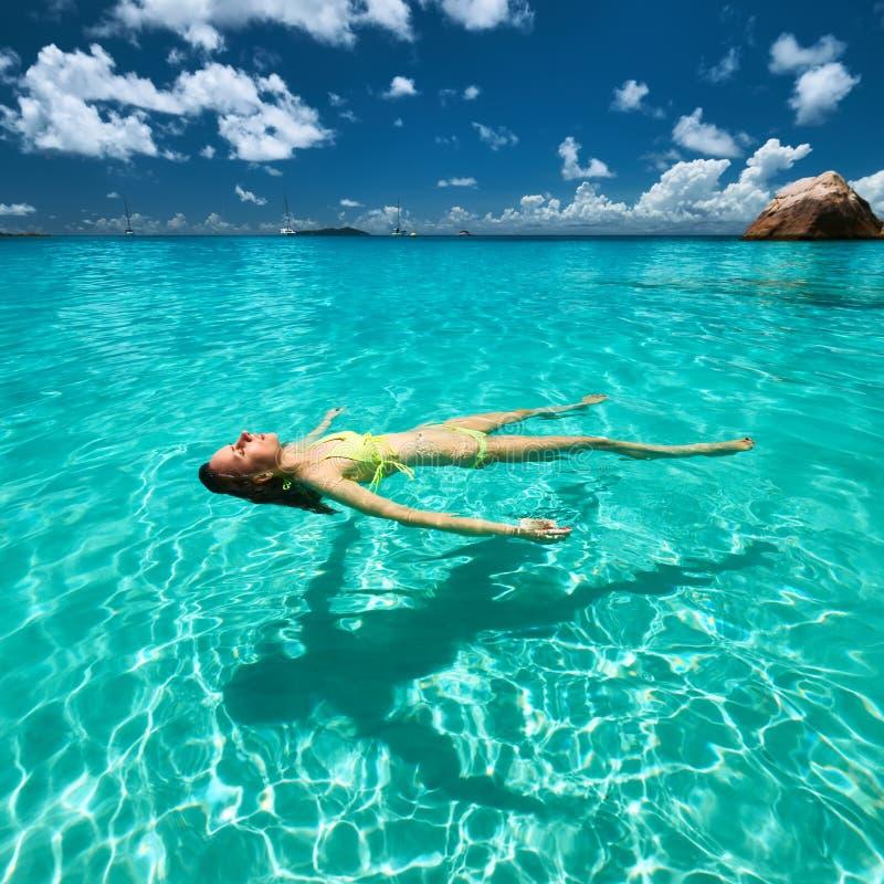 Kvinna i den gula bikinin som ligger på vatten royaltyfri bild