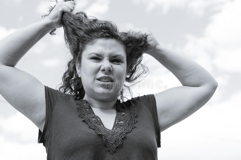 Kvinna i den negativa inställningen som drar hennes hår fotografering för bildbyråer