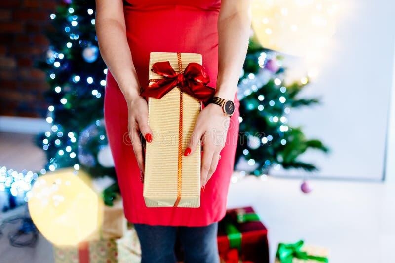 Kvinna i den röda klänningen som ger julgåvan i guld- ask med det röda bandet arkivfoto