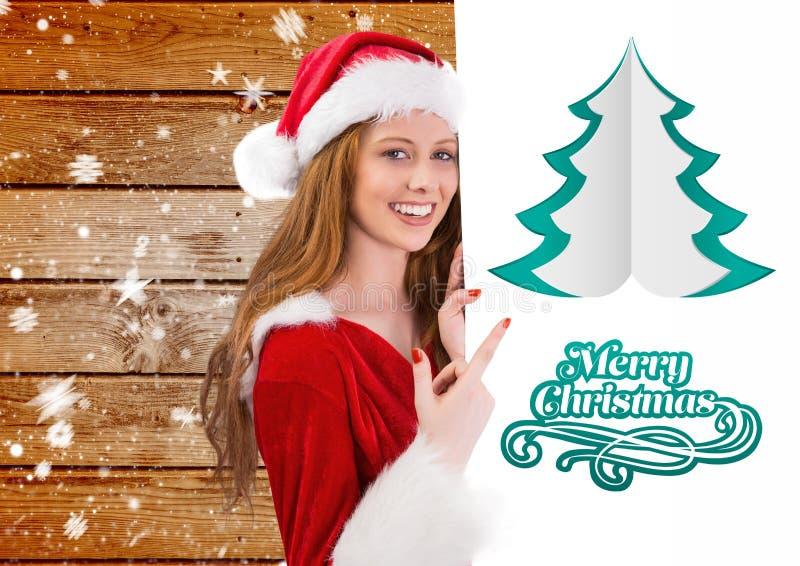Kvinna i den santa dräkten som pekar på plakatet som önskar glad jul arkivfoton