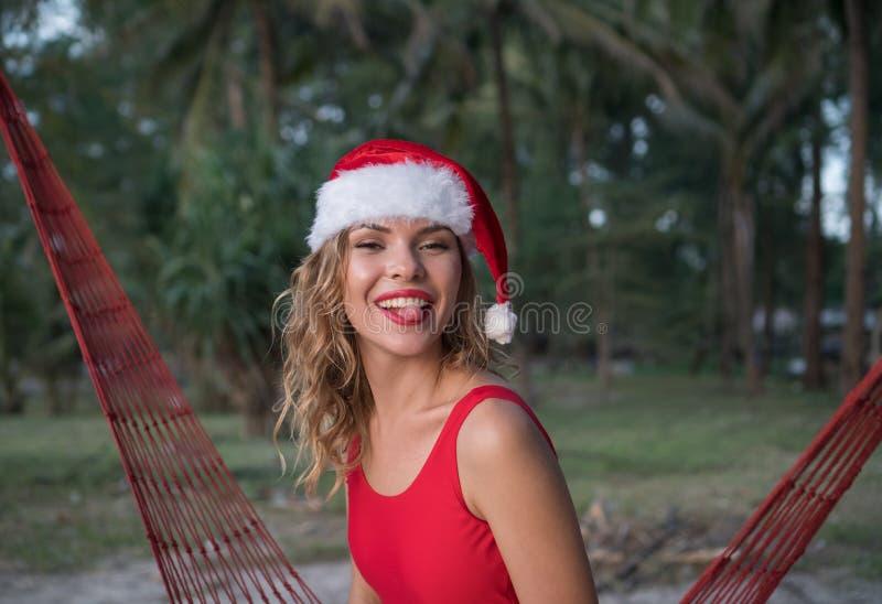 Kvinna i den santa hatten på hängmattan på stranden fotografering för bildbyråer