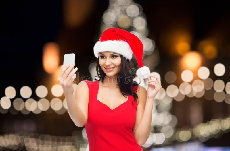 Kvinna i den santa hatten som tar selfie vid smartphonen royaltyfri bild