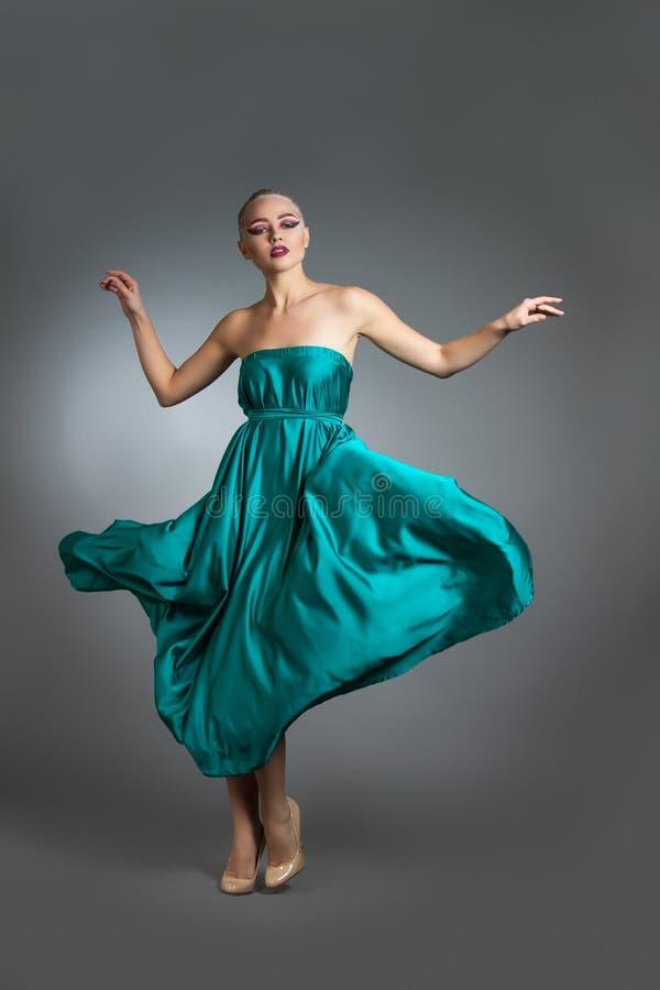 Kvinna i den siden- klänningen som vinkar på vind Flyga och fladdra kappatorkduken över grå bakgrund arkivfoto