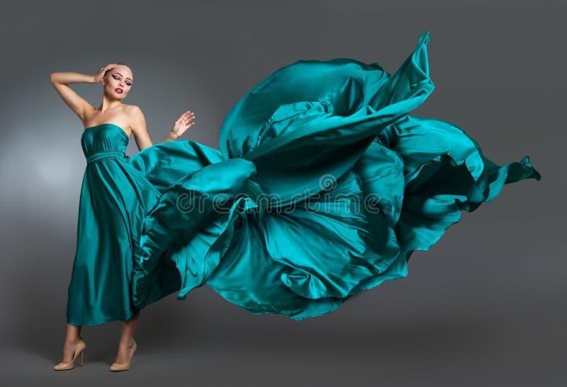 Kvinna i den siden- klänningen som vinkar på vind Flyga och fladdra kappatorkduken över grå bakgrund arkivfoton