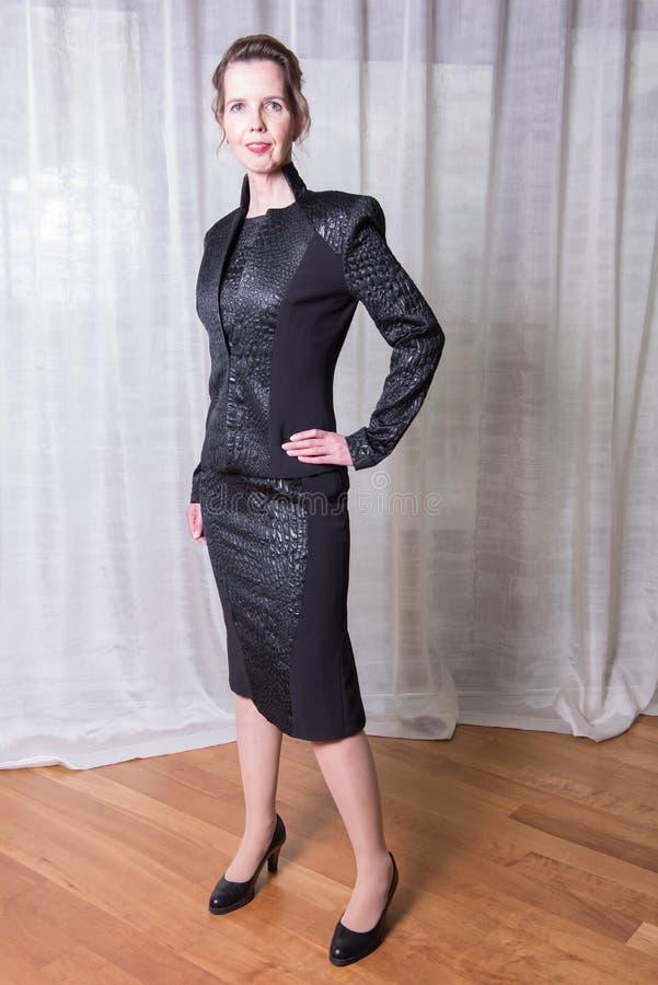 Kvinna i den svarta klänningen som ut går i aftonen arkivfoto