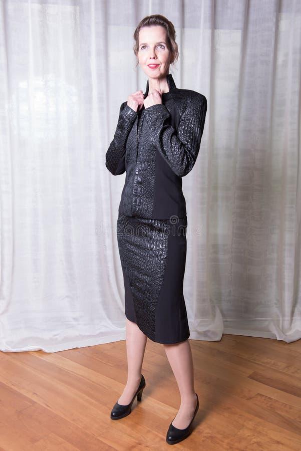 Kvinna i den svarta klänningen som ut går i aftonen royaltyfri foto