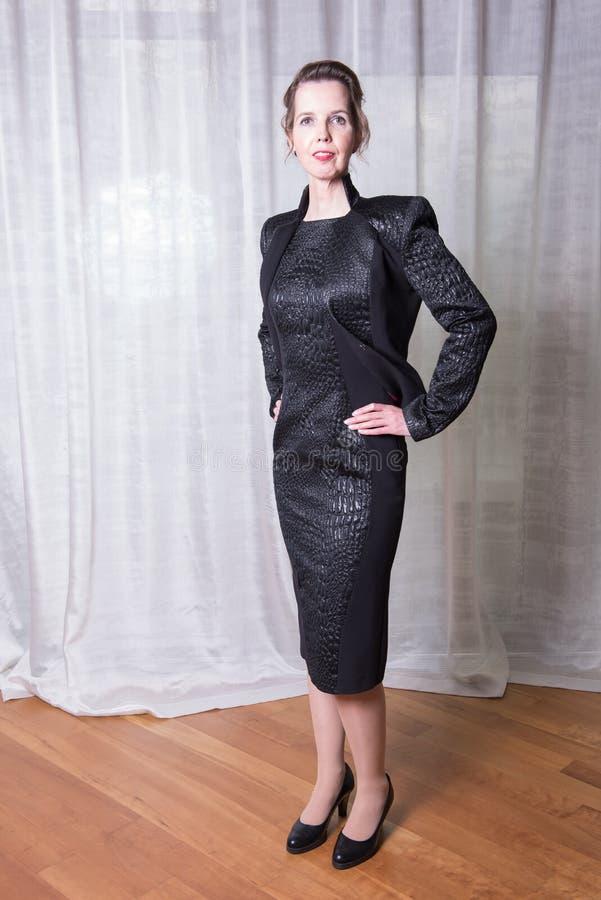 Kvinna i den svarta klänningen som ut går i aftonen arkivbilder