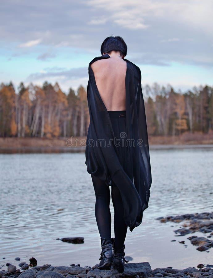 Kvinna i den svarta near floden royaltyfri fotografi