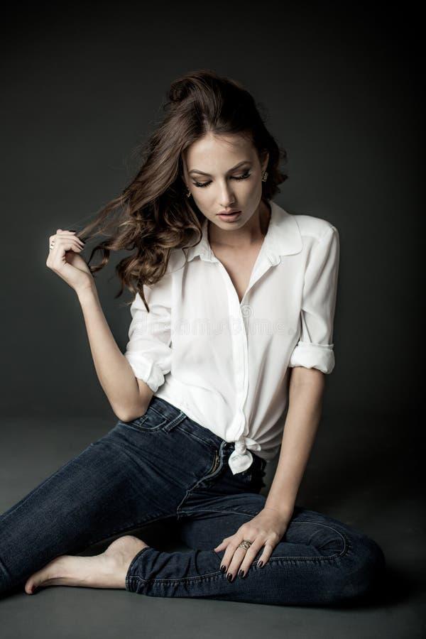 Kvinna i den vit blusen och jeans arkivfoto