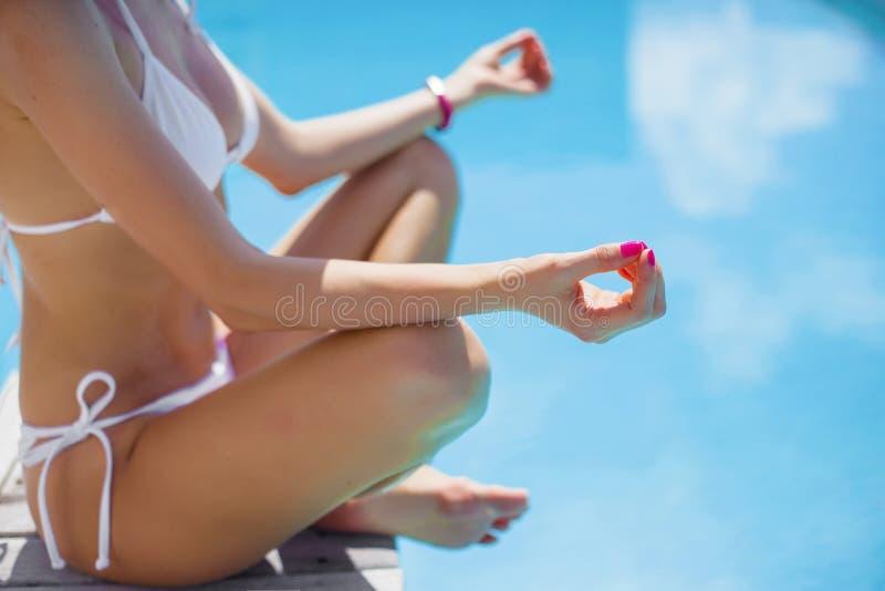 Kvinna i den vita bikinin som mediterar vid simbassängen arkivbilder