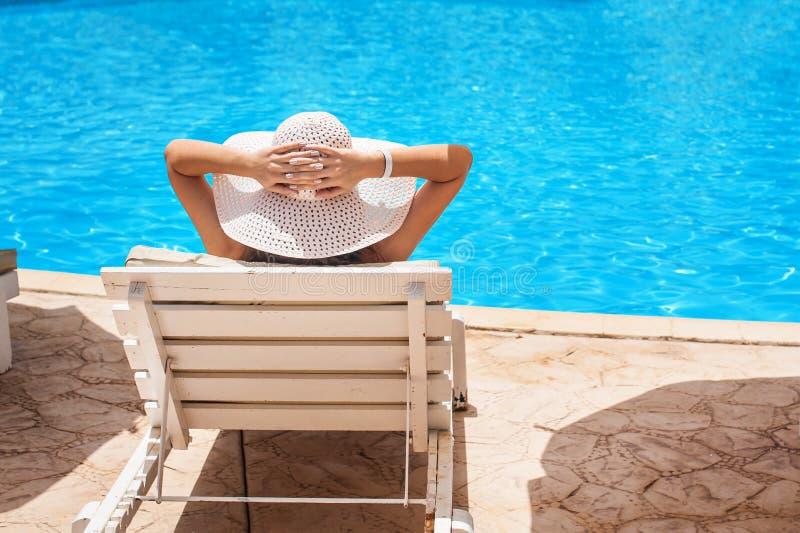 Kvinna i den vita hatten som ligger på en dagdrivare nära simbassängen royaltyfri foto